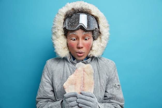 Shocked embarrassed afro american woman stares at frozen fish feels comfortable in warm clothing wears ski goggles enjoys winter holidays feels frosty during good time.