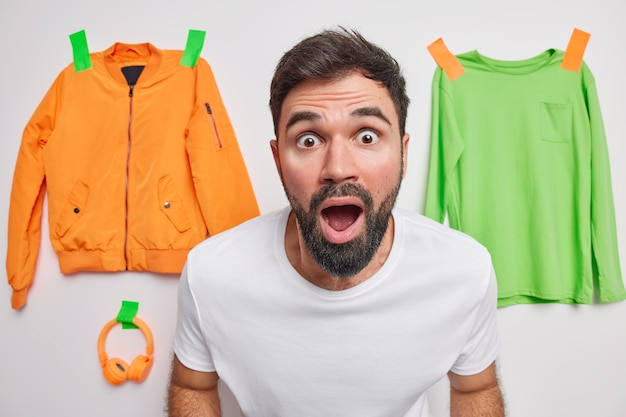 Shocked embarrassed bearded adult man stares at front keeps mouth wide opened from amazement cannot believe in shocking news poses indoor with clothes items plastered to wall in wall