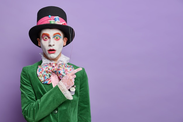 Shocked embarrassed hatter on masquerade party indicates at upper right corner stunned by something horrible isolated over purple wall shows empty space for your information