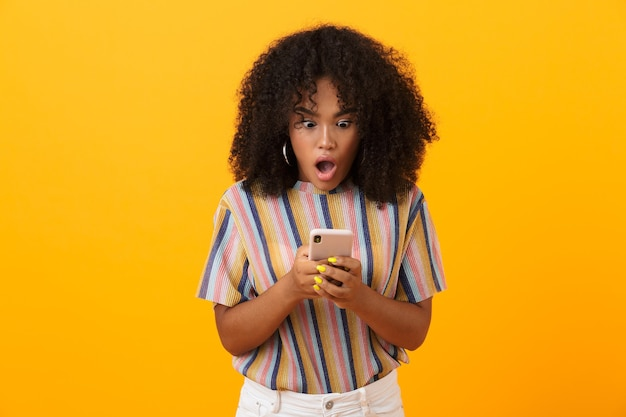 Shocked emotional african woman posing isolated over yellow space using mobile phone.