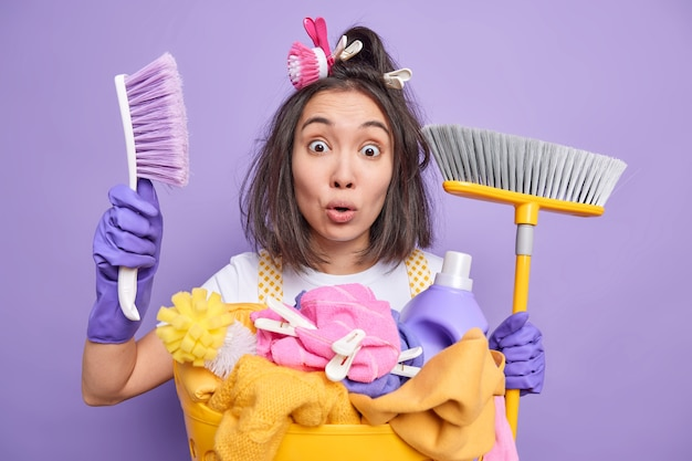 Shocked emotional asian woman stares bugged eyes at camera holds brush and broom cannot believe in something being on guard of cleanliness busy with household duties isolated over purple wall