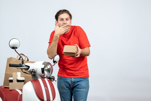 Shocked and emotional delivery man in red uniform standing near scooter holding small box on white background