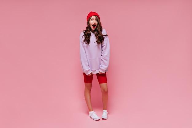 赤いショートパンツと紫色のパーカーでショックを受けた感情的な女の子がカメラをのぞきます