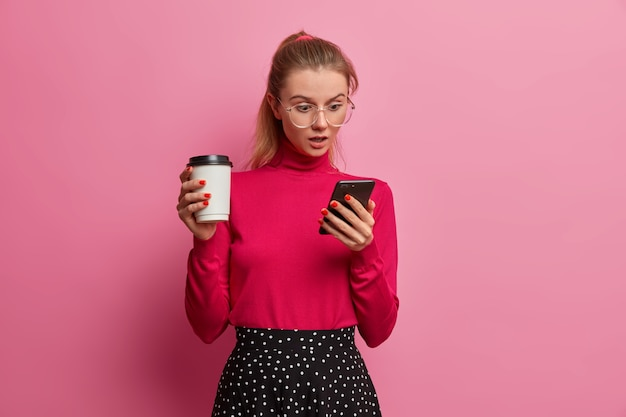 Shocked emotional girl stares at smartphone display, chats with friends online, wears big optical glasses, holds disposable cup of fresh drink, enjoys tasty coffee