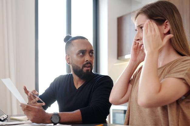 월별 모기지 지불을 잊은 아내를 바라보는 청구서를 손에 들고 충격을 받은 감정적인 남자