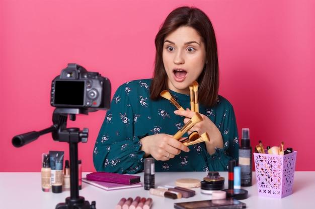 Шокированная эмоциональная девушка записывает видео о том, как делали лайфхаки, широко раскрывает рот, держит в руках разные кисти для макияжа, выглядит удивленной. концепция красоты, стиля и блоггера.