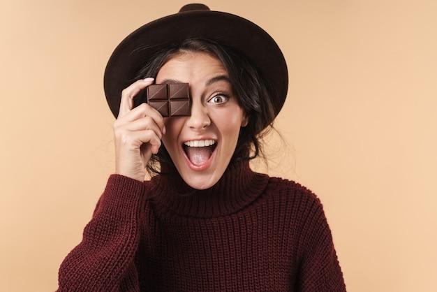 Потрясенная эмоциональная молодая симпатичная женщина, изолированная над бежевой стеной, держащей шоколад.