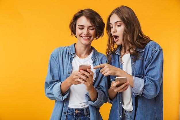 携帯電話を使用して黄色の壁の上に孤立してポーズをとるショックを受けた感情的な若い女性の友人。