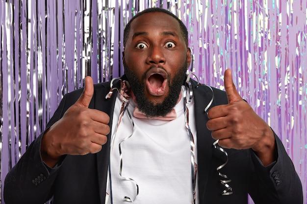 Шокированный этнический мужчина открывает рот от удивления, смотрит в камеру, поднимает палец вверх, очарованный чем-то крутым