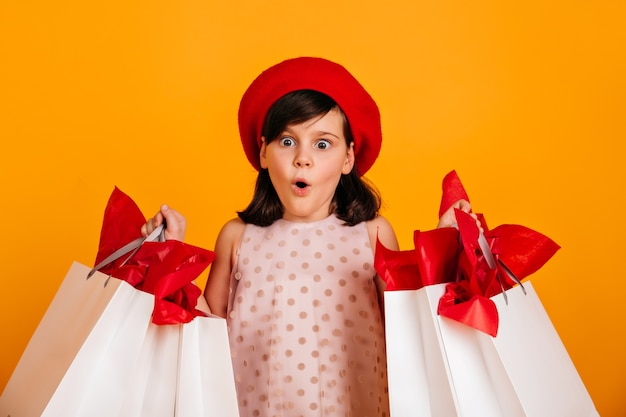 Шокирован европейский ребенок позирует после покупок. ребенок держит магазинные сумки с открытым ртом.