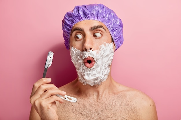 Shocked european man holds shaving blade, applies foaming gel on cheeks, shaves bristle, wears purple protective showercap, has hygiene routine