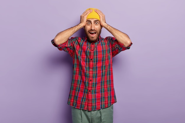 충격을받은 유럽 남자는 노란색 모자와 체크 무늬 셔츠를 입고 머리에 손을 얹고 표정을 궁금해하고 보라색 배경에 포즈를 취하고 끔찍한 것에 두려워했습니다. 무서워하는 남자 실내