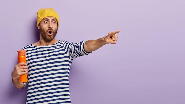 충격을받은 유럽인 남자가 거리를 가리키고, 놀라운 것을 발견하고, 뜨거운 커피와 함께 주황색 보온병을 들고, 세련된 모자와 줄무늬 스웨터를 입고