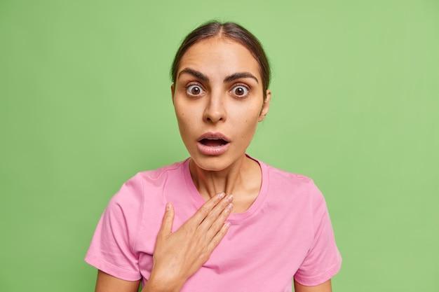La donna europea scioccata trattiene il respiro tiene la bocca aperta non può credere a scioccanti notizie mozzafiato indossa abiti casual isolati sul muro verde