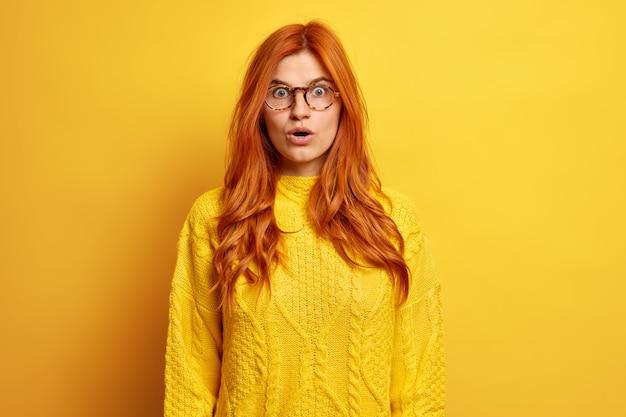 Шокированная европейская женщина с рыжими натуральными волосами держит рот открытым с ошеломленным выражением лица, затаив дыхание, одетая в вязаный свитер.