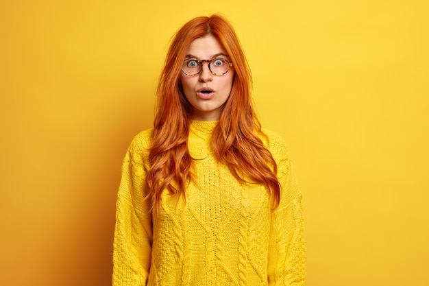 Shocked european woman with red natural hair keeps mouth opened has stunned expression holds breath dressed in knitted sweater.