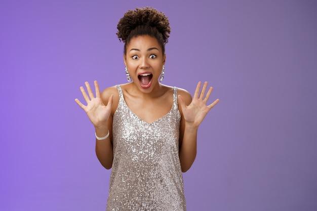 Scioccato eccitato affascinante donna afro-americana in abito scintillante d'argento alza i palmi divertito urlando entusiasta meravigliato spalancando gli occhi ricevono incredibile incredibile sorpresa, sfondo blu.