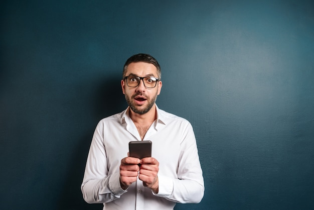 Shocked excited man using mobile phone.