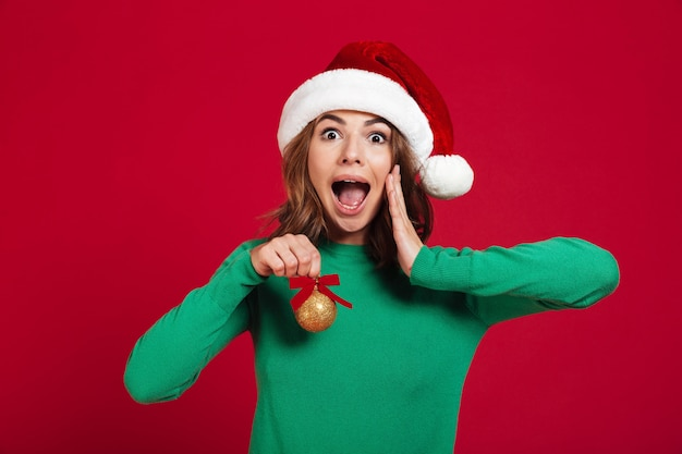 Shocked excited young lady wearing christmas santa hat