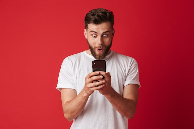 Shocked excited young man using mobile phone.