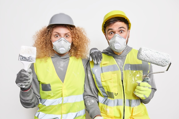 Shocked experienced maintenance workers paint apartment busy doing renovation repair and redecoration hold tools wear protective respirators hardhats and uniform