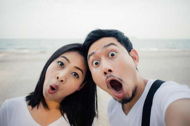 Shocked face of couple tourist on romantic beach vacation trip.