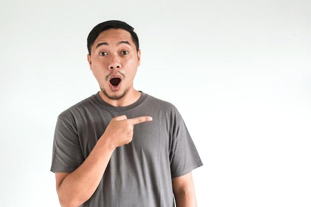 白い背景で隔離の灰色のtシャツでアジア人男性のショックを受けた顔の表情