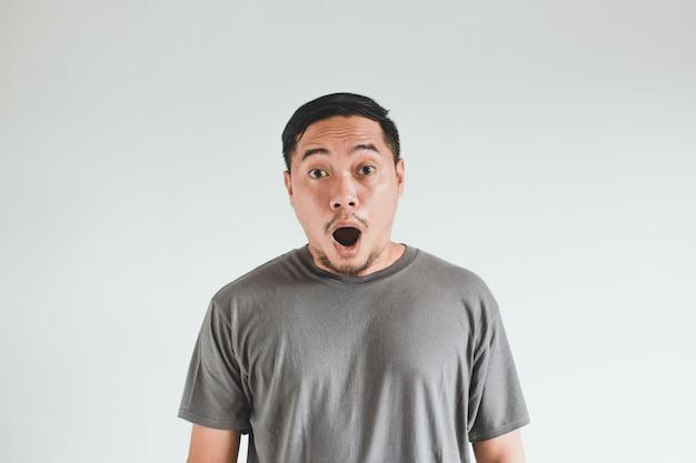 白い背景の上の灰色のtシャツでアジア人男性のショックを受けた表情