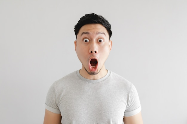 Shocked face of man in grey t-shirt and grey wall.