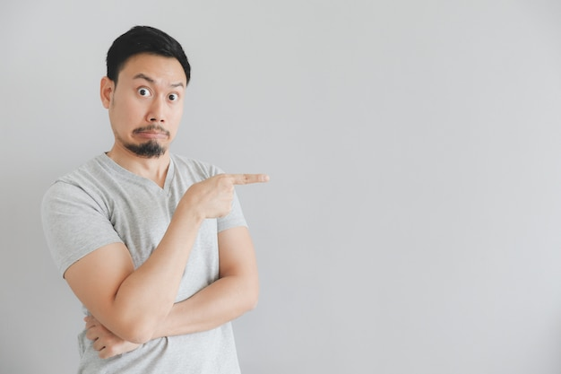 Shocked face of man in grey t-shirt with hand point on empty space.
