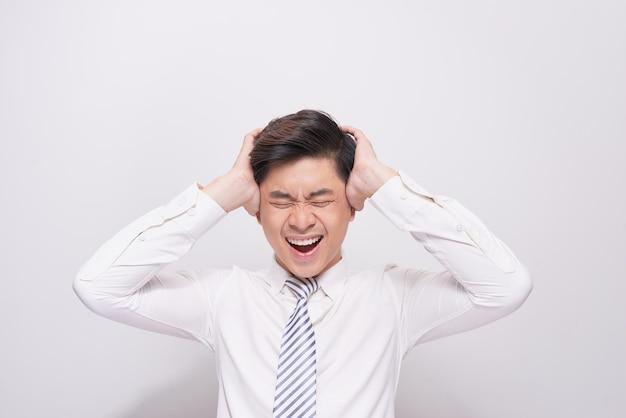회색 배경에 흰색 셔츠를 입은 아시아 남자의 충격된 얼굴.
