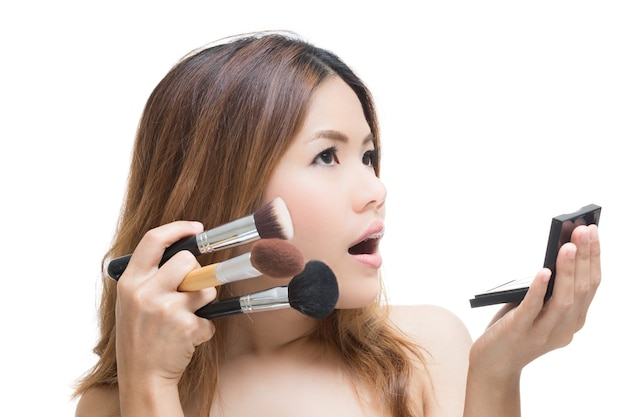 Shocked face woman with hand holding make up brush and palette