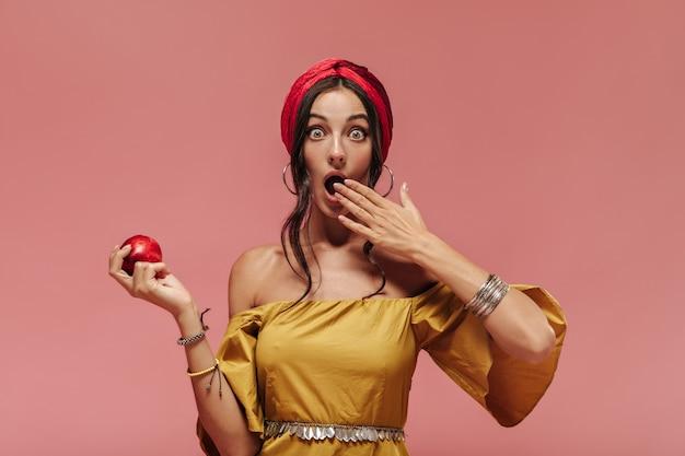 Donna alla moda scioccata con accessori fantastici e vestito giallo che guarda nella telecamera e tiene in mano una mela rossa sul muro rosa pink