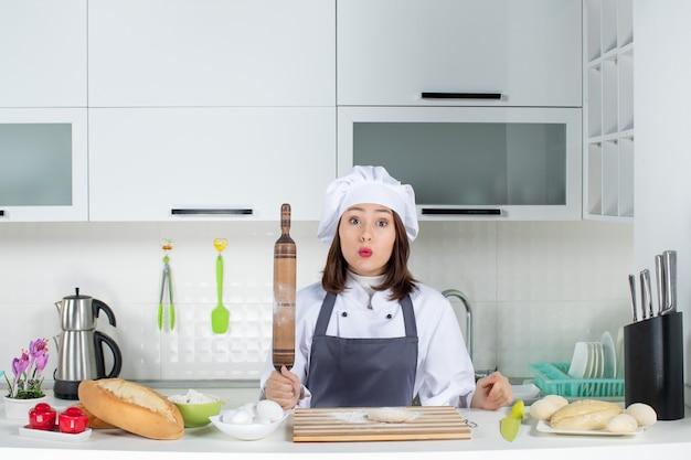 Scioccato chef commis femminile in uniforme in piedi dietro il tavolo che prepara la pasticceria nella cucina bianca