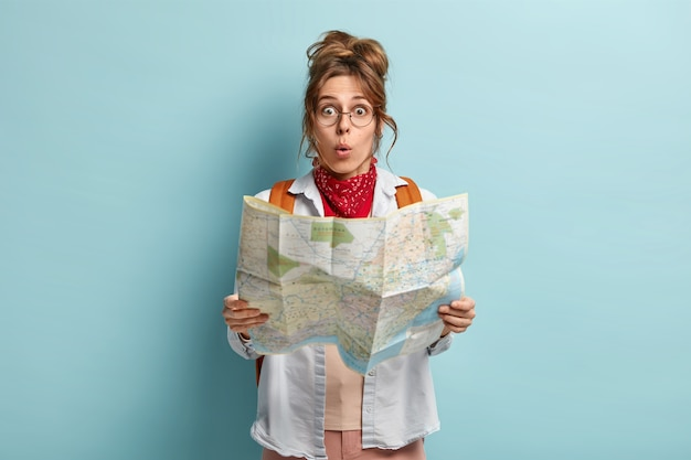 Shocked female european tourist has tour around world, surprised to loose way, reads map