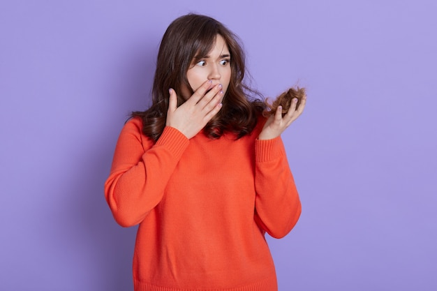 Shocked female having problems with hair loss, holding curl and covering mouth with palm, lady wearing casual orange jumper, being frustrated of balding problems, isolated over blue wall.