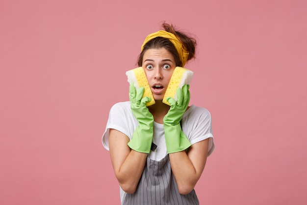 Shocked female housekeeper holding two sponges on cheeks having much work to do being in panic. caucasian woman with surprised and excited look wearing apron and protective gloves for cleaning