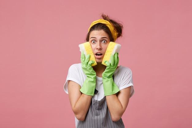 ショックを受けた女性の家政婦が頬にスポンジを2つ持って、パニック状態になるために多くの仕事をしている。クリーニングのためのエプロンと保護手袋を着用して驚いて、興奮した表情の白人女性