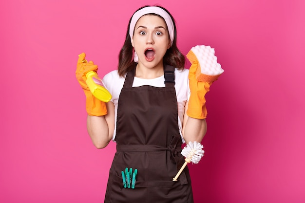 Shocked female housekeeper holds sponge and detergent spray in hands, having much work to do. attractive woman with surprised and excited look wearing apron and protective gloves. copy space.