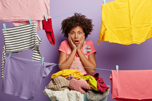 Shocked female housekeeper stands near clothes line, basin of laundry