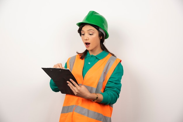 Shocked female industrial engineer in uniform with clipboard on white background.
