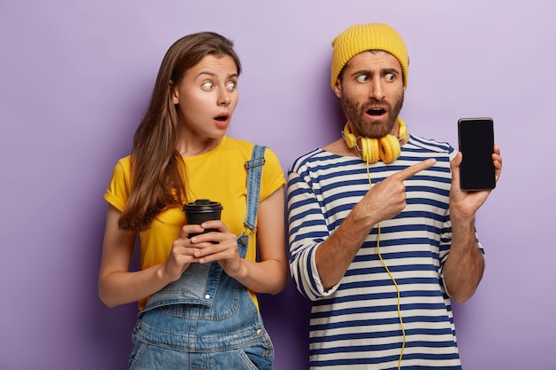 Shocked female and male friends point at smartphone display, show mockup screen, woman holds takeaway coffee, dressed in denim overalls, stand next to each other in studio.