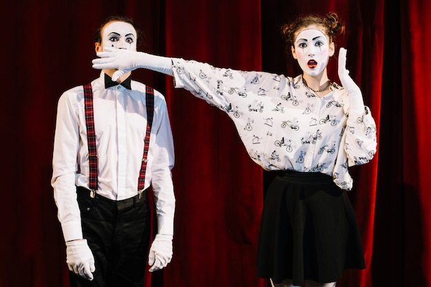 Shocked female mime artist covering male mime's mouth standing in front of curtain