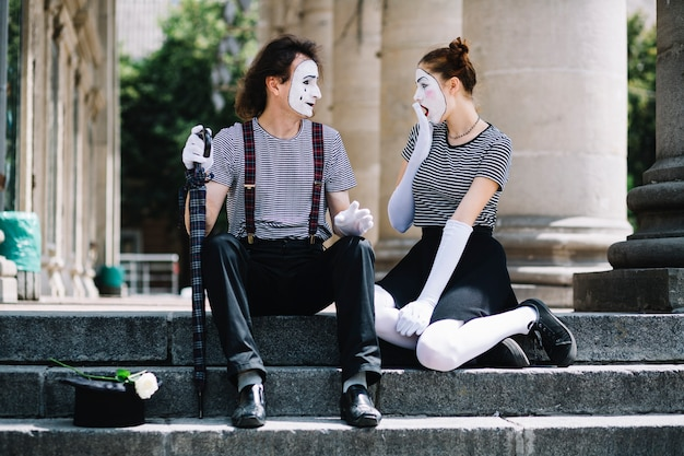 Shocked female mime artist looking at male mime
