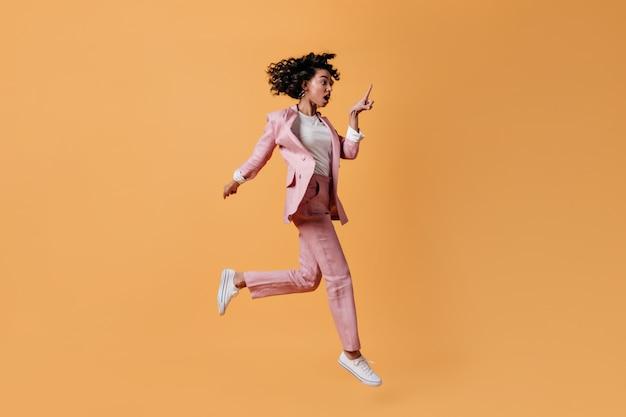 黄色の壁にジャンプするショックを受けた女性モデル