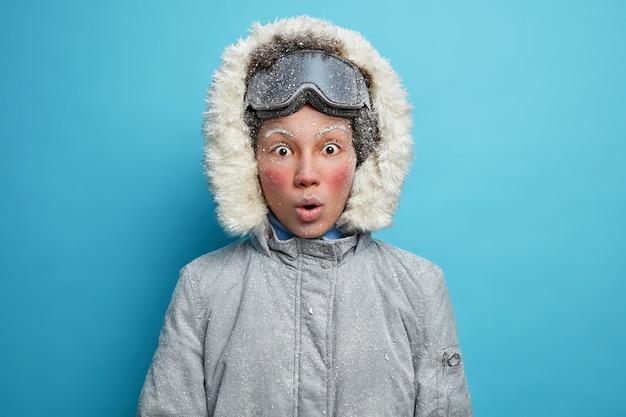 Sciatore femminile scioccato con la faccia rossa congelata guarda vestito con una giacca grigia con cappuccio e occhiali da snowboard.