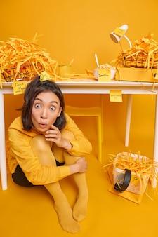 Una studentessa scioccata scopre la scadenza per prepararsi all'esame si siede sul pavimento sotto il desktop nello spazio di coworking ascolta notizie scioccanti che gli studi da casa si preparano per la sessione di esame