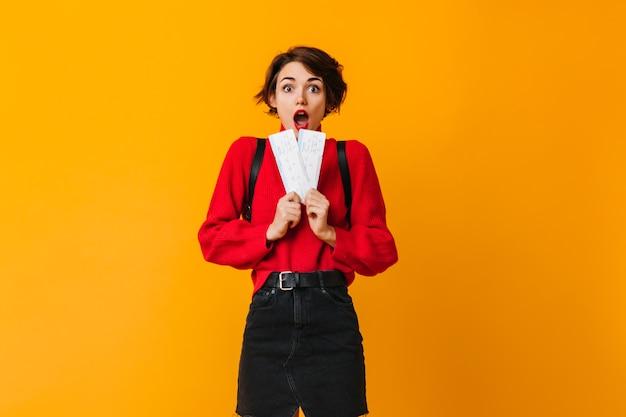 Shocked female tourist holding tickets