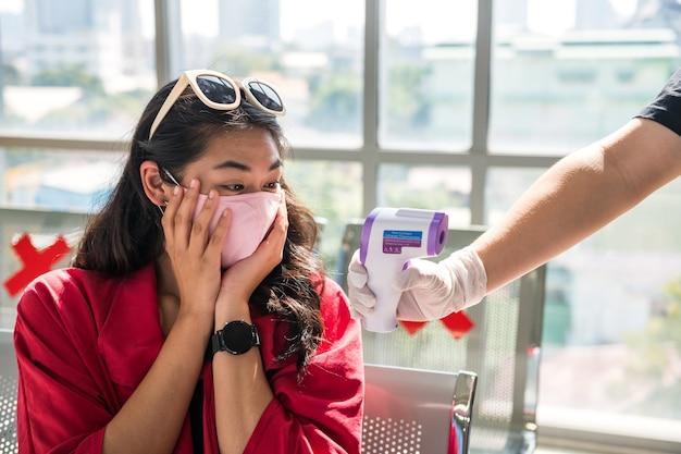 마스크를 쓴 충격을받은 여성 여행자는 장교의 손에 의료용 적외선 온도계로 그녀의 높은 체온을 봅니다.