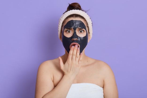 Шокированная женщина с черной увлажняющей маской на лице, прикрывая открытый рот ладонью